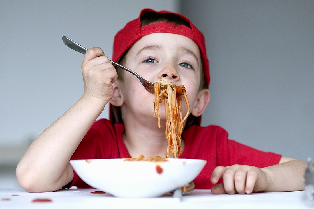 A little boy eating spaghetti with tomato sauce