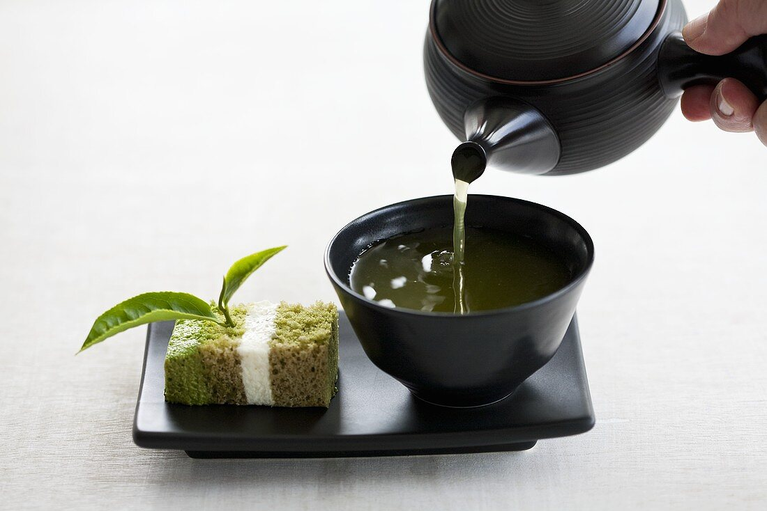 Green tea being poured with a piece of tea cake next to the cup