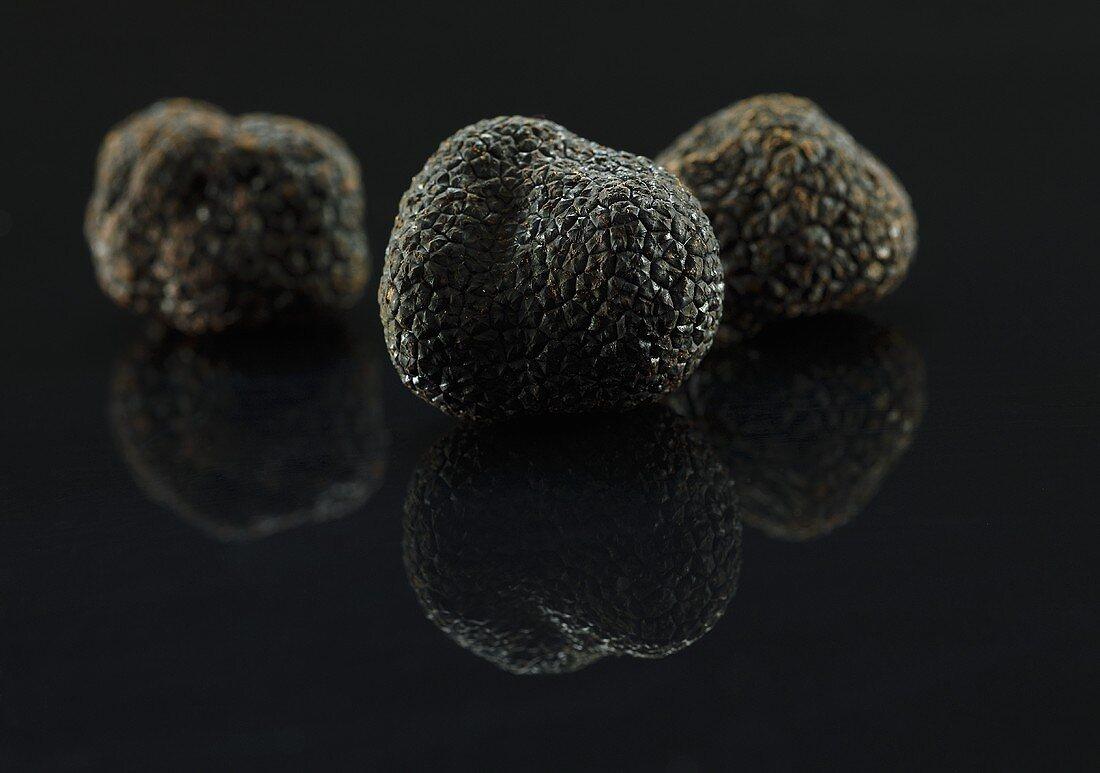 Black truffles on a black surface
