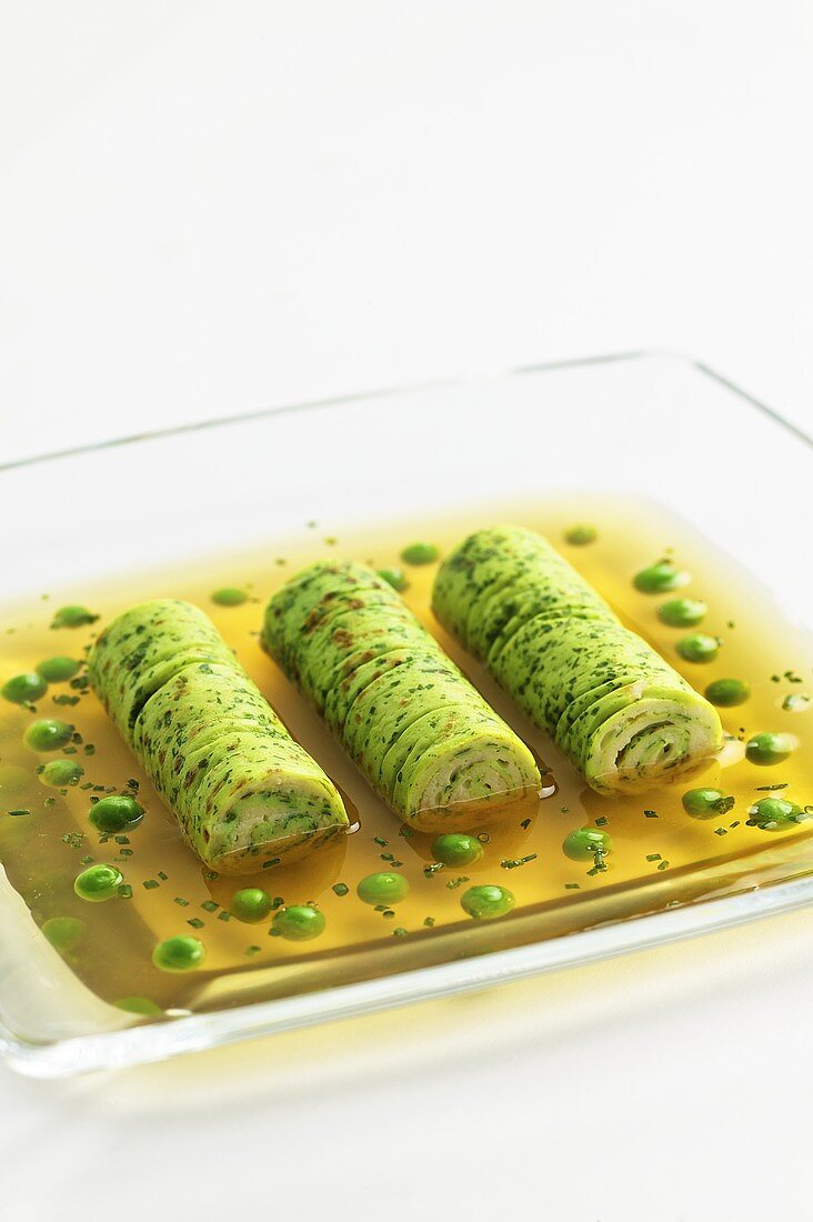 Clear beef stock with herb pancake roulade