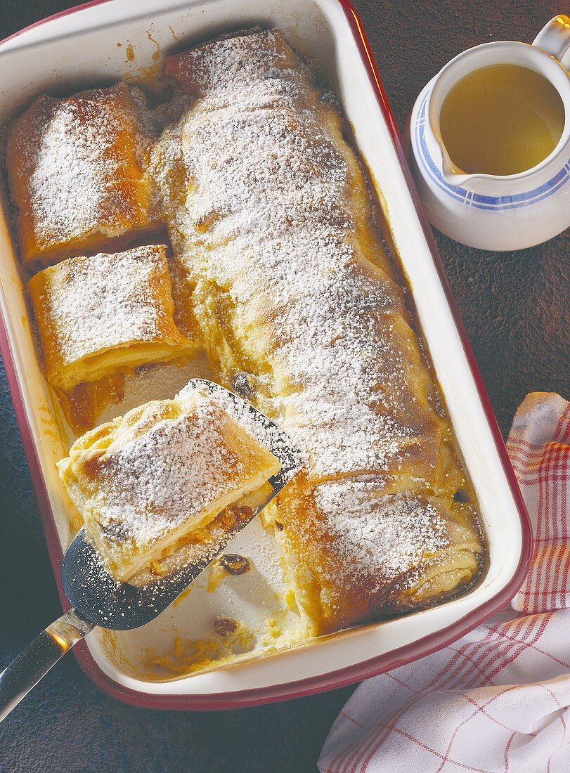 Curd cheese strudel with icing sugar in baking dish