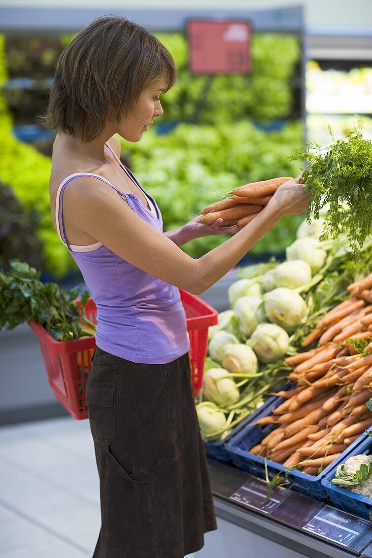 Young woman buying carrots in a supermarket