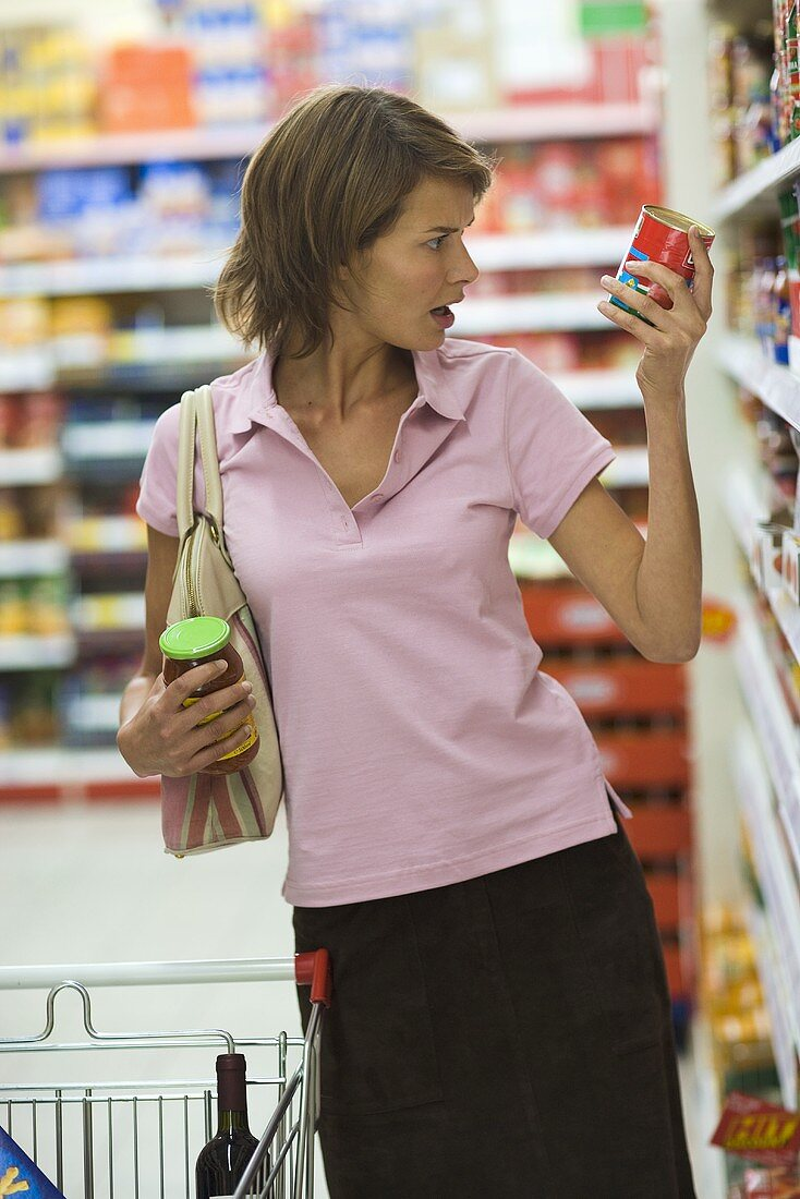 Young woman shopping, holding a food tin in her hand