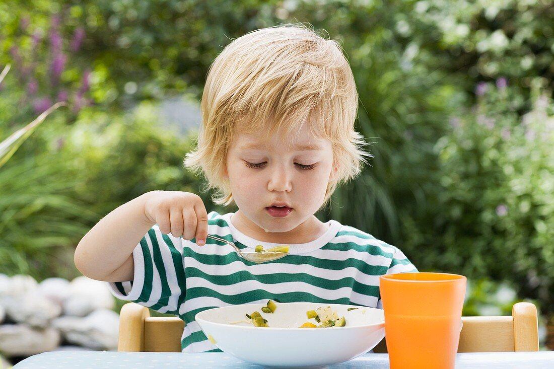 Blond boy eating vegetable soup