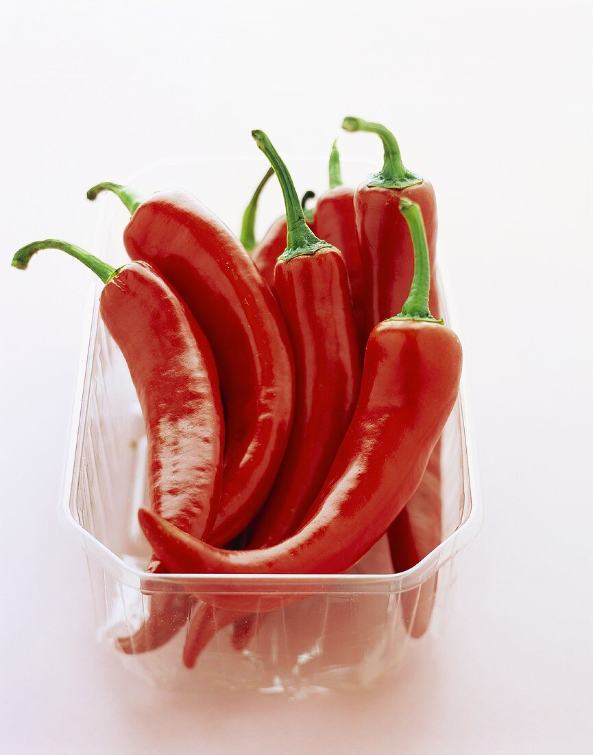 Fresh red chili peppers in plastic container