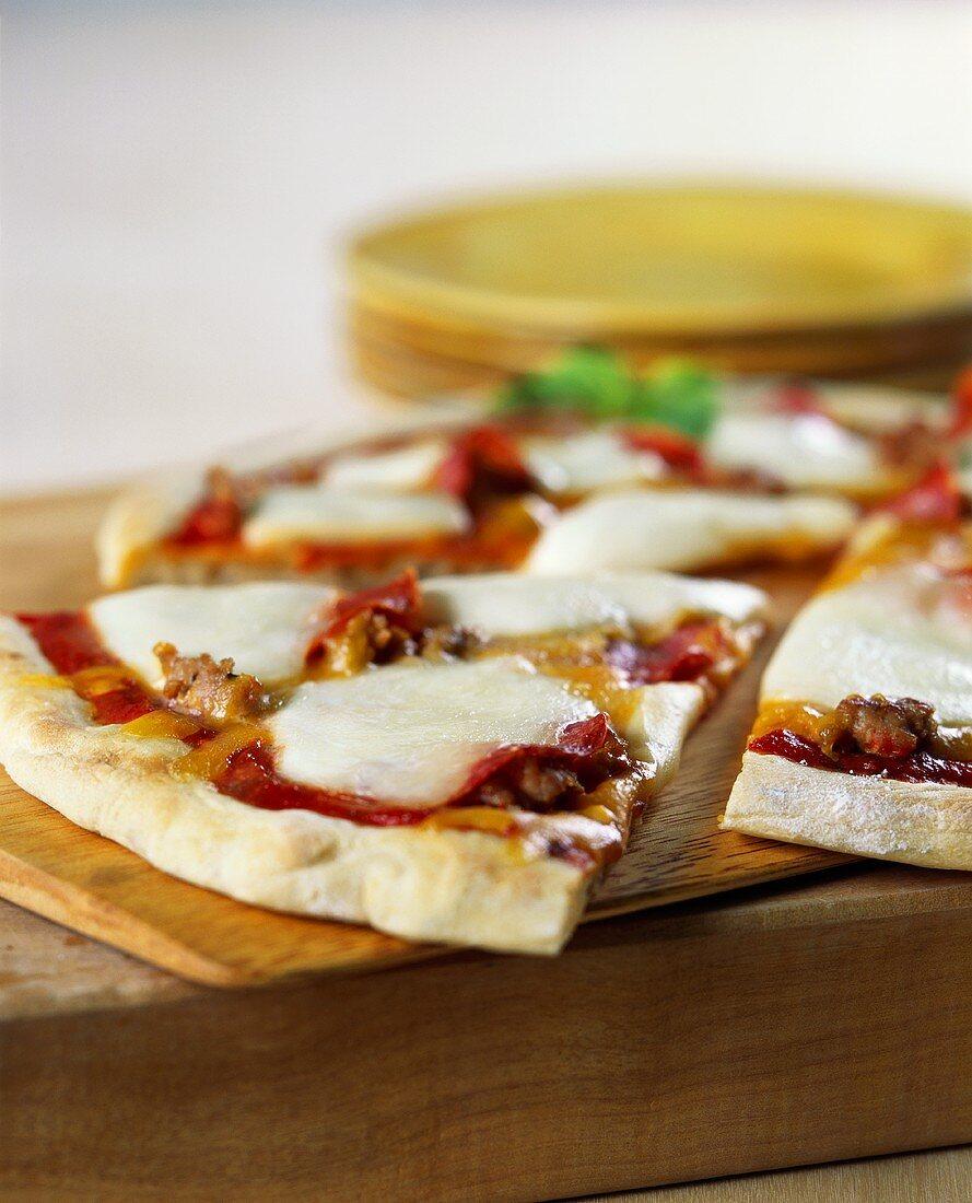 Pizza with sausage and mozzarella, a piece cut