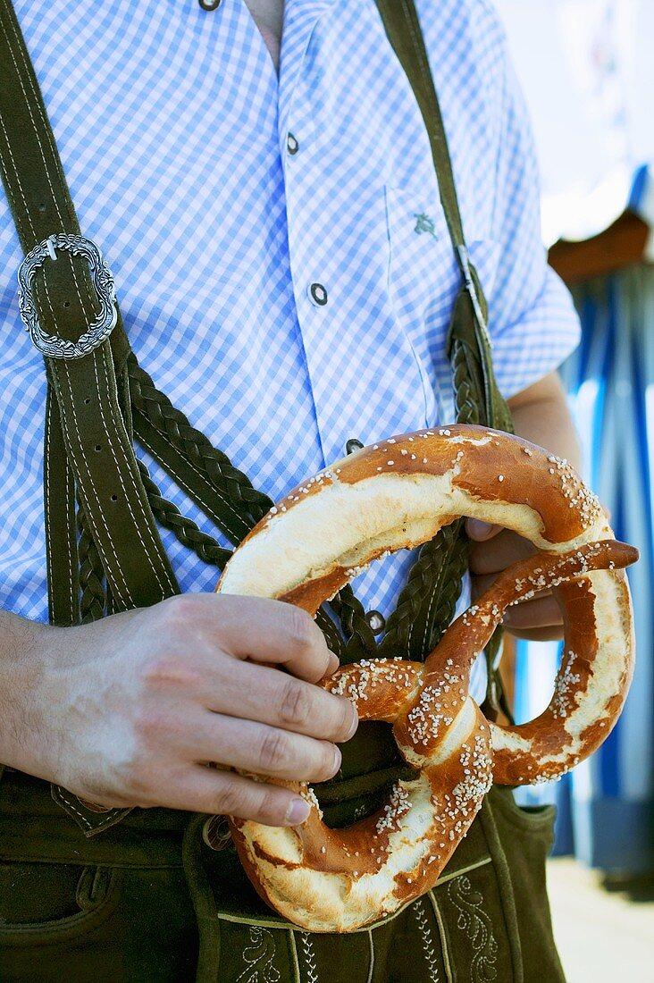 Man in national dress with pretzel (Oktoberfest, Munich)