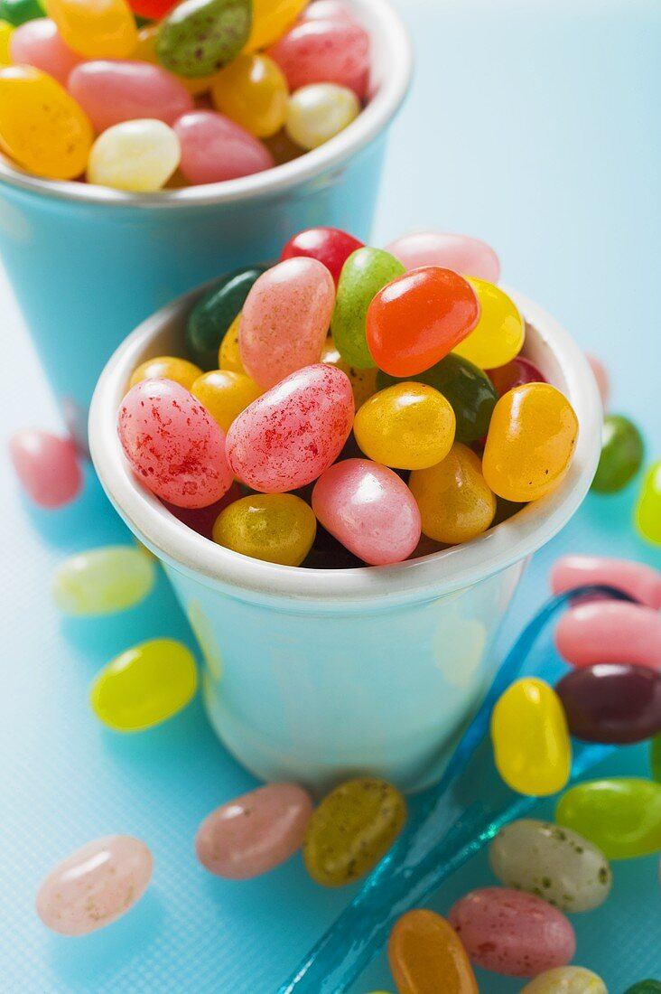 Coloured jelly beans in beakers