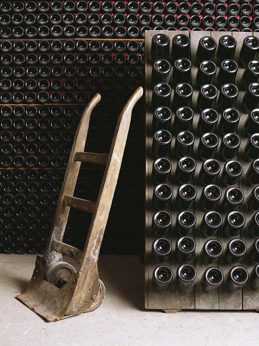 Stacked wine bottles in wine cellar, barrow