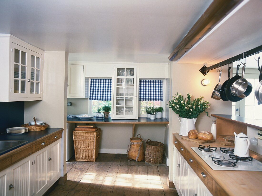 Rustic kitchen with white cupboards and gas cooker