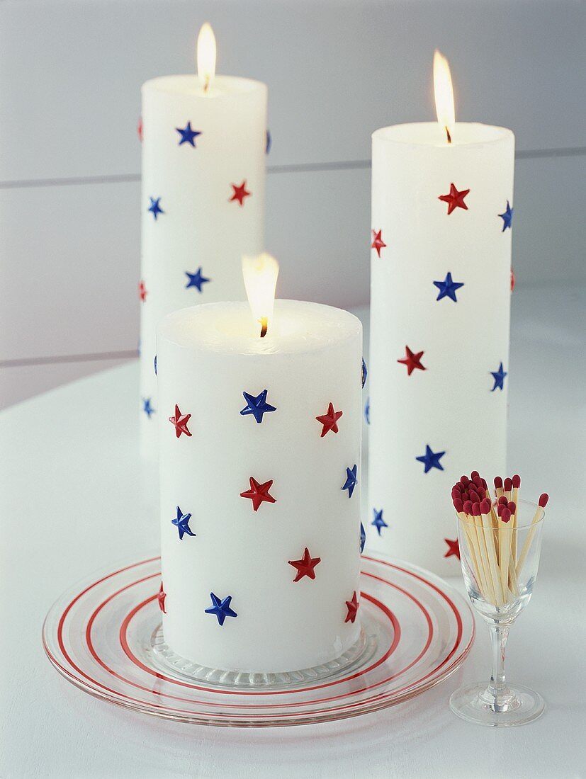 White candles with red and blue stars, matches