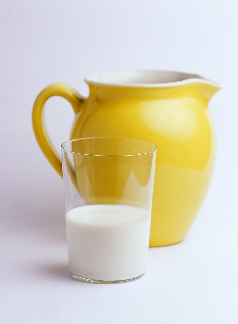 A glass of milk and a milk jug