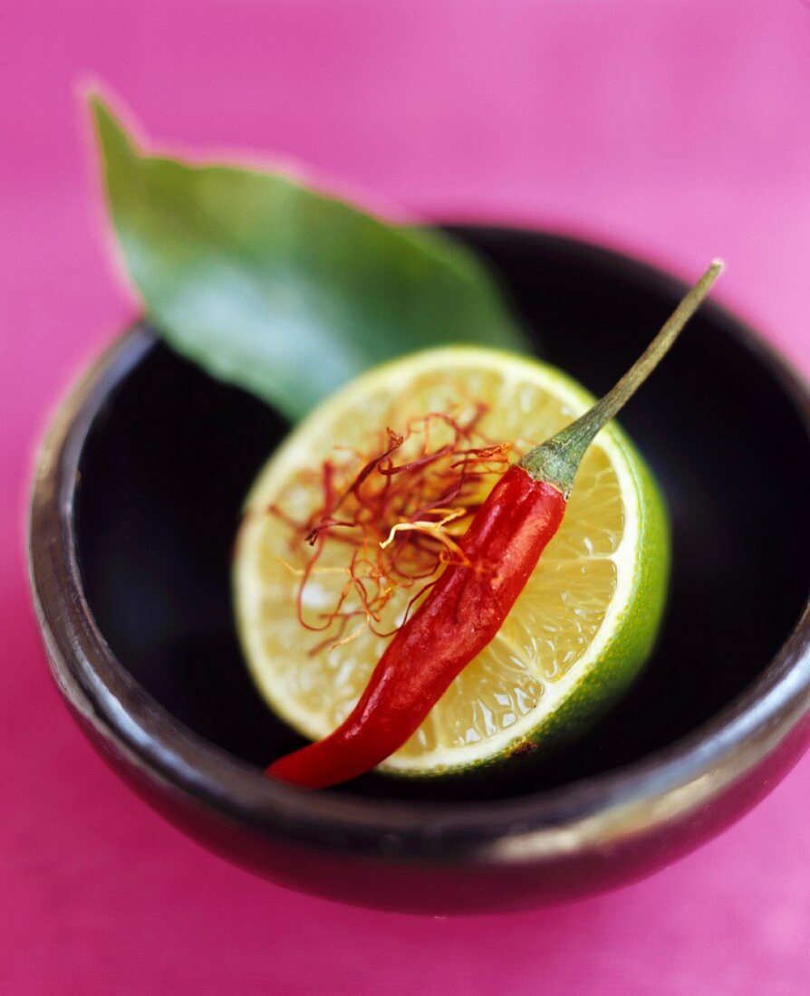 Still life with lime, chili, saffron and kaffir lime leaf