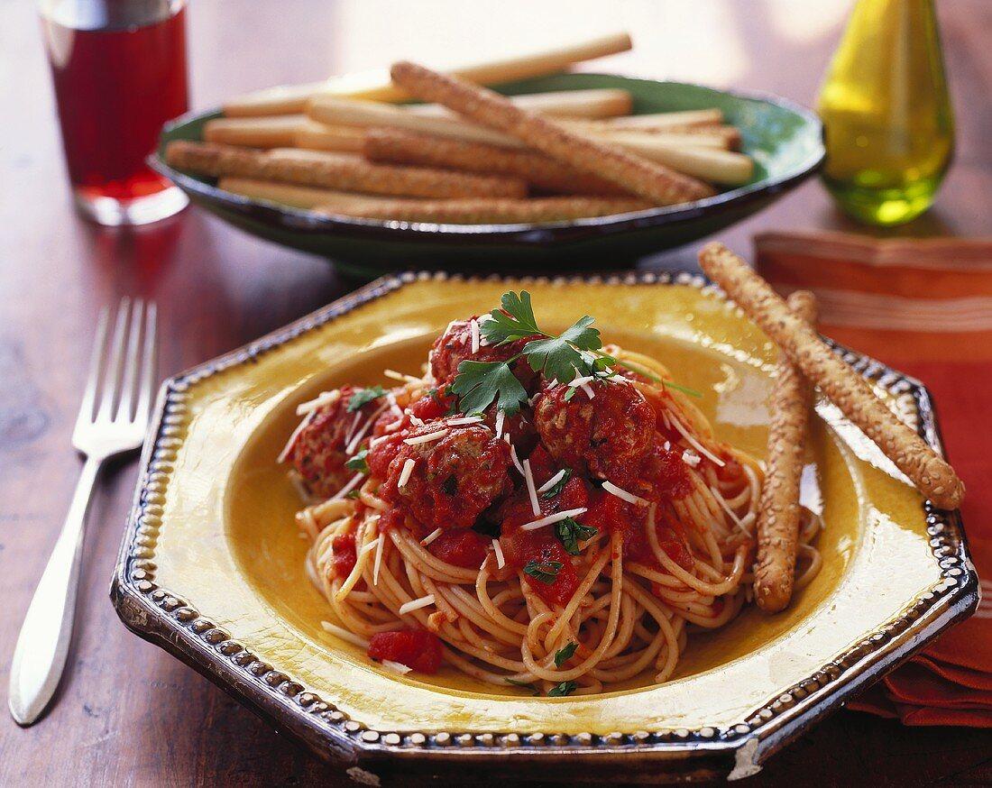 Spaghetti with meatballs, tomato sauce and sesame sticks