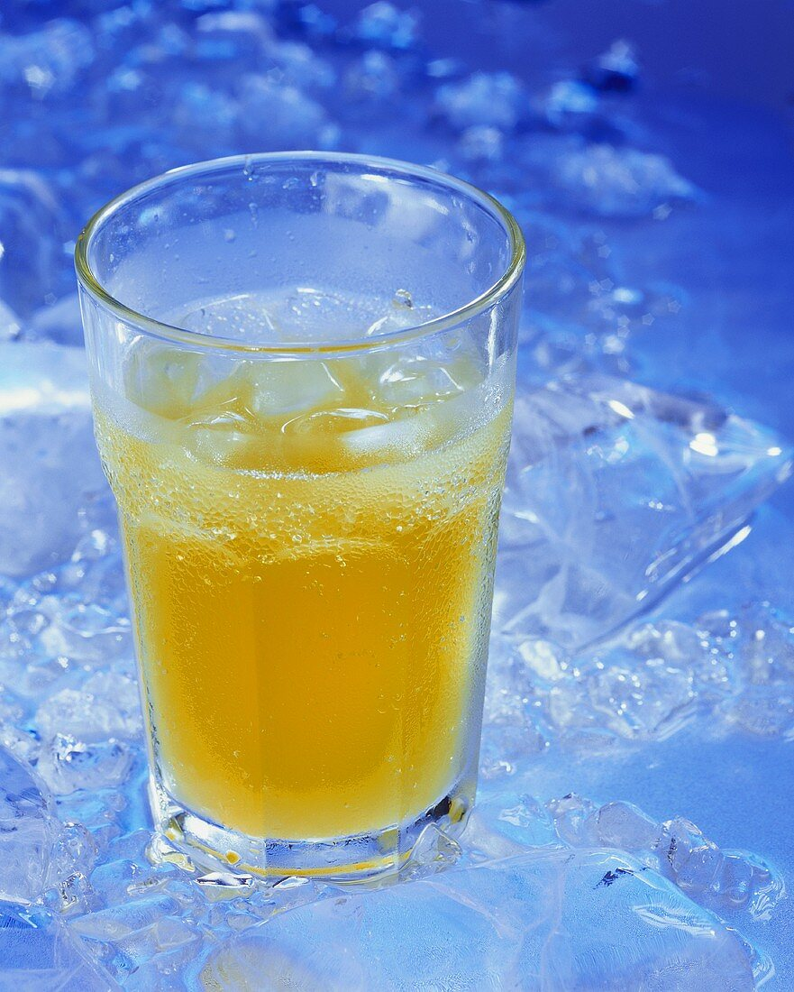 A glass of orangeade with ice cubes
