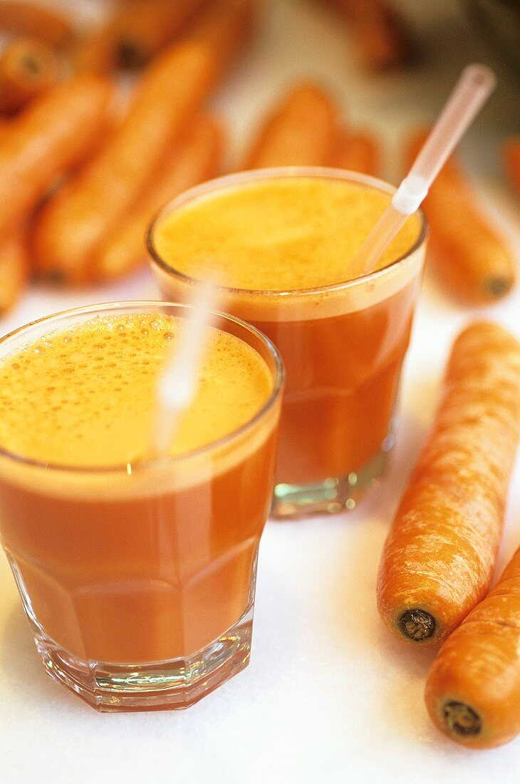Freshly pressed carrot juice and carrots