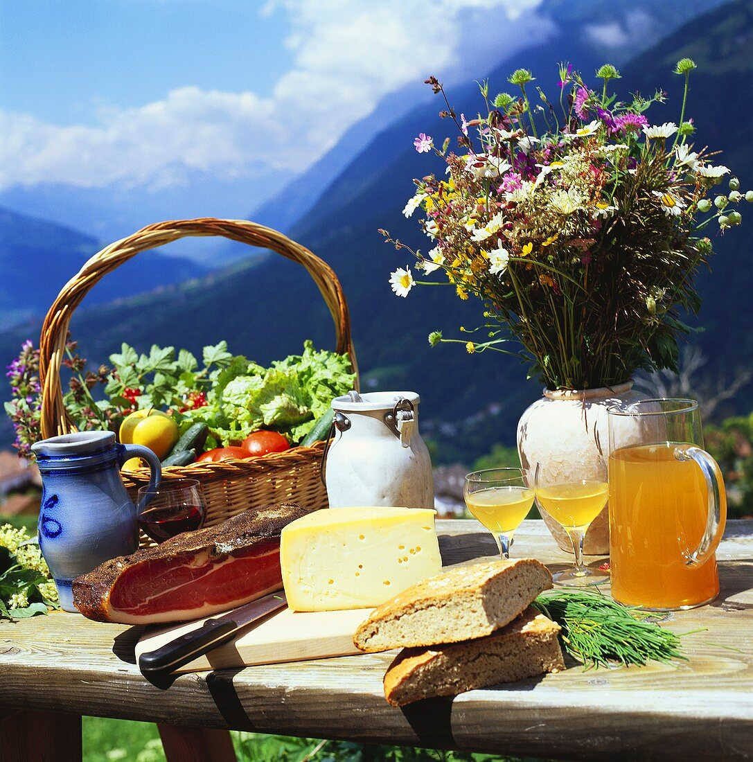 Cheese, bread, vegetables etc. on table in mountain landscape