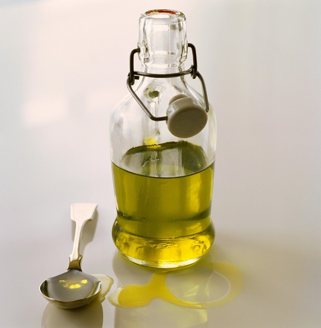 Native olive oil in a bottle and on a spoon