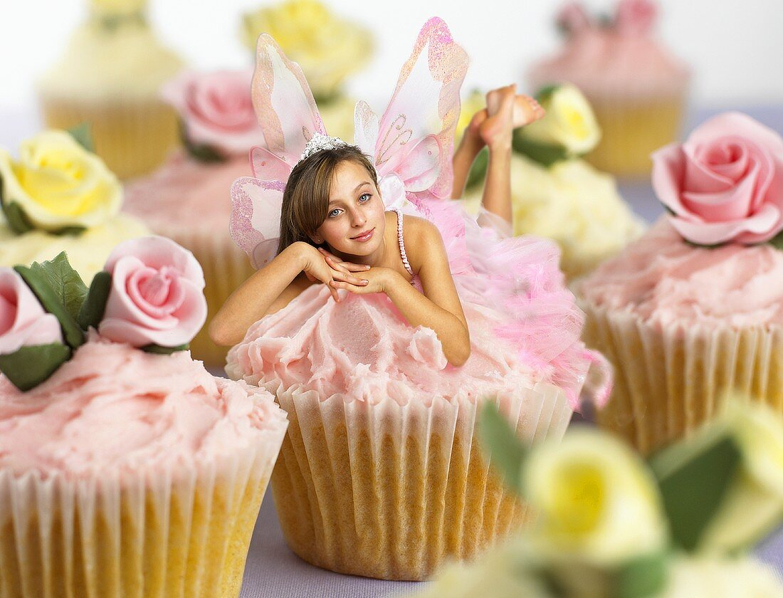 Cupcakes with pink cream & young woman as fairy (Fairy Cake)