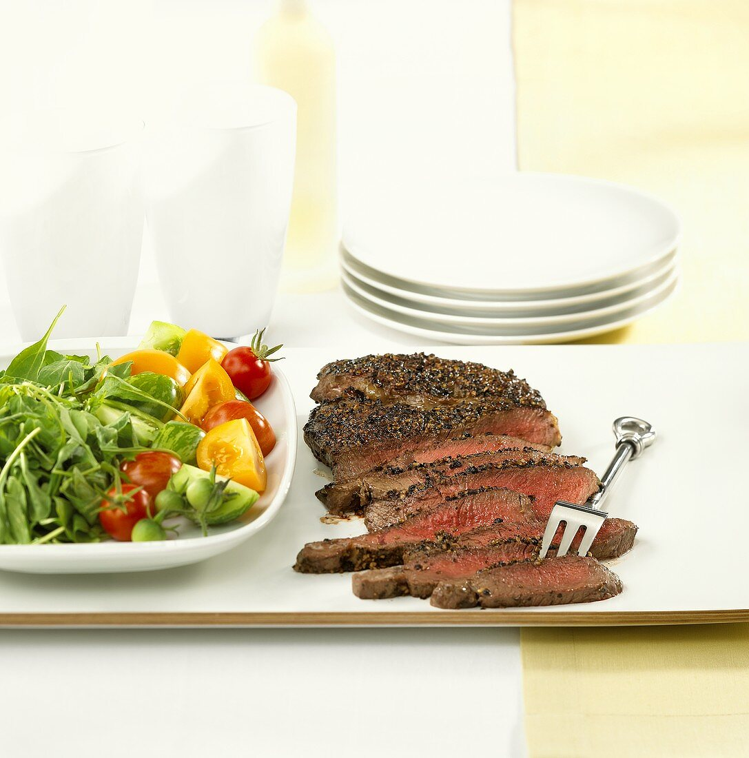 Beef steak with pepper crust and salad