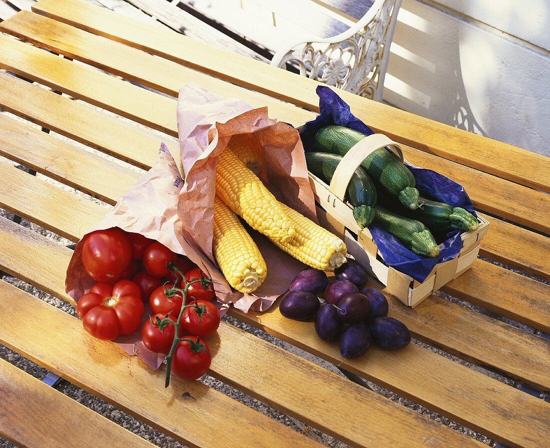 Plums, tomatoes, corncobs and courgettes in paper bags