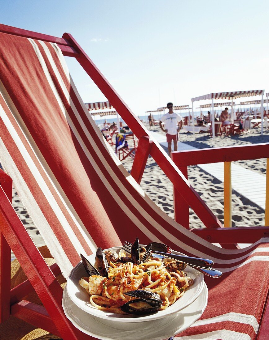 Linguine with seafood on deckchair on beach