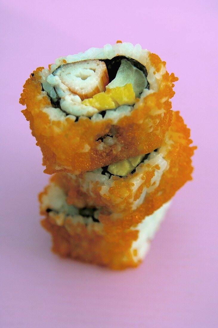 Three sushi rolls in a pile