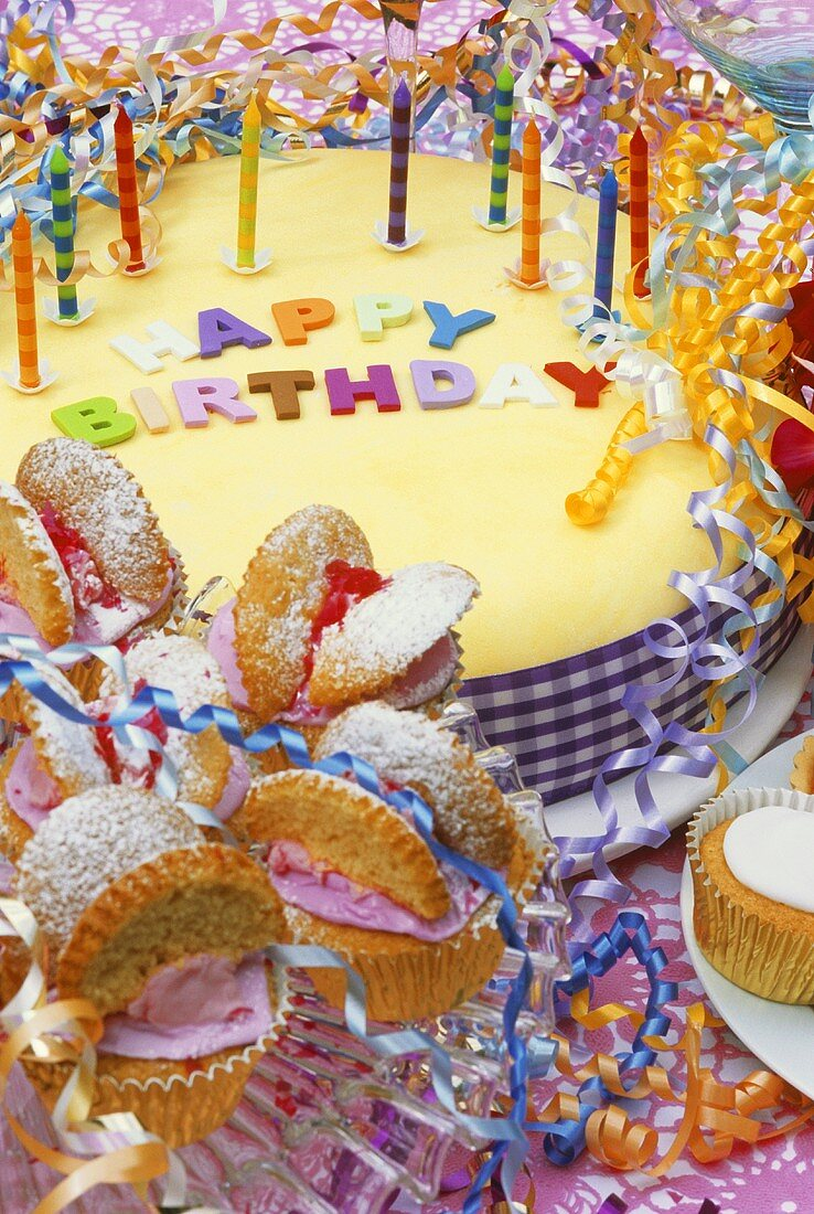 Party table with birthday cake and buns