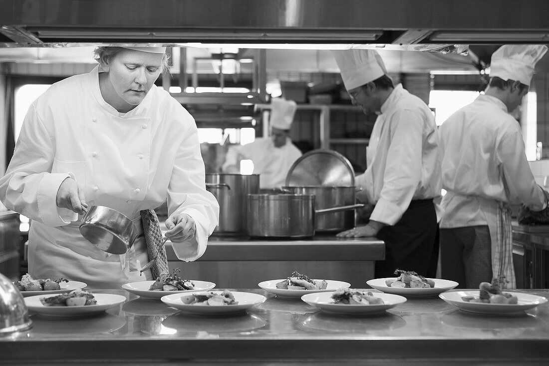 Female chef pouring sauce over main courses