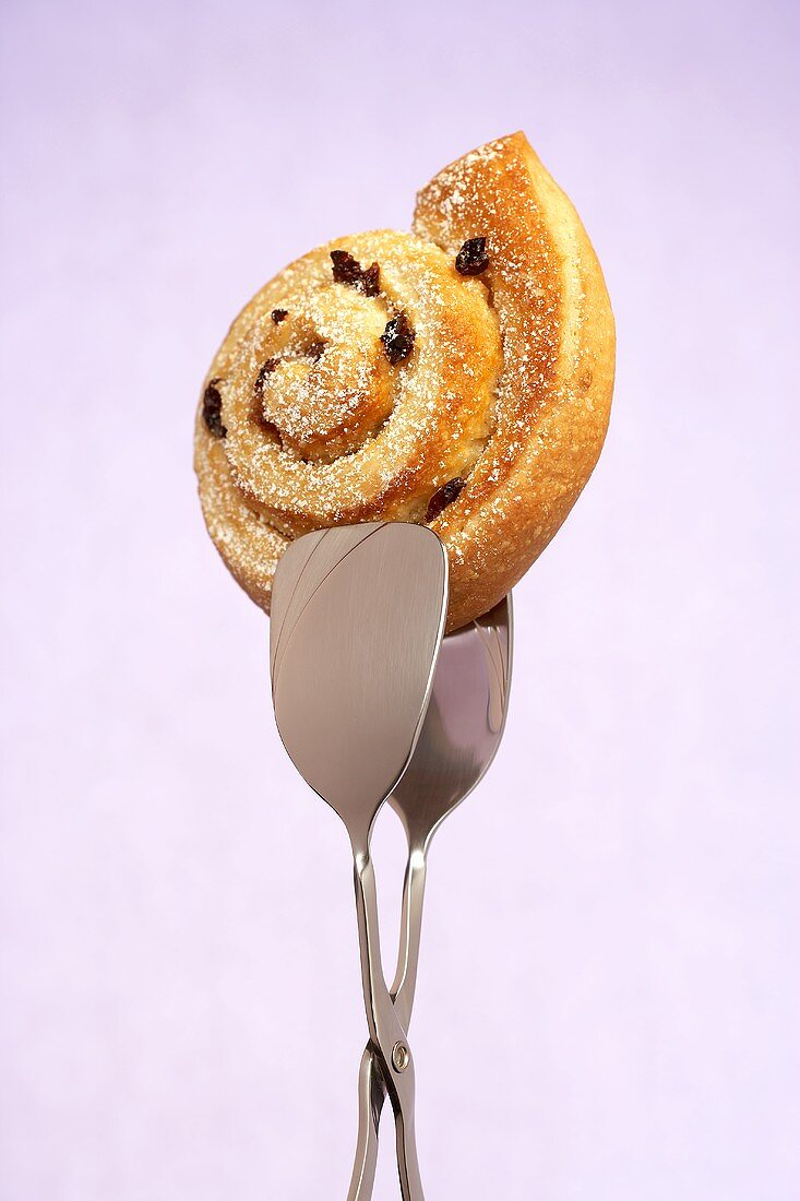 A raisin snail in cake tongs