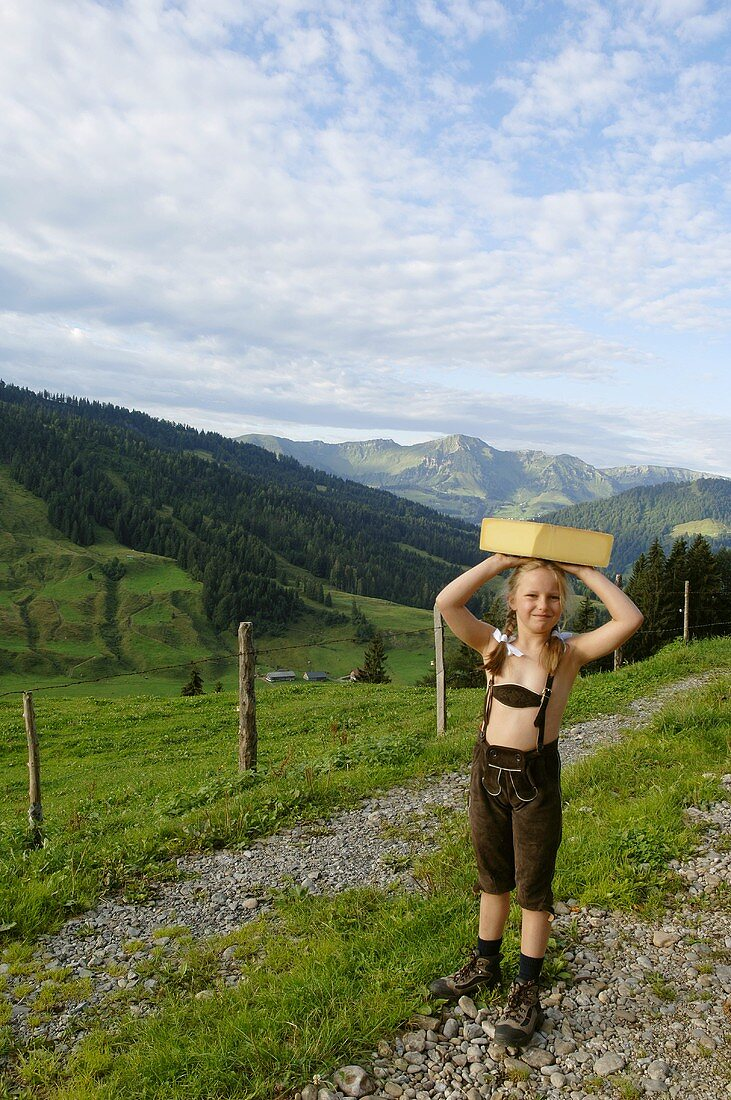 Girl holding a Bergkäse cheese above her head