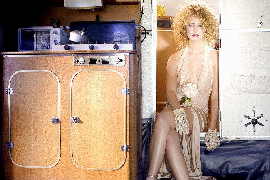 Junge Frau im Abendkleid sitzt im Einstieg eines Wohnwagens