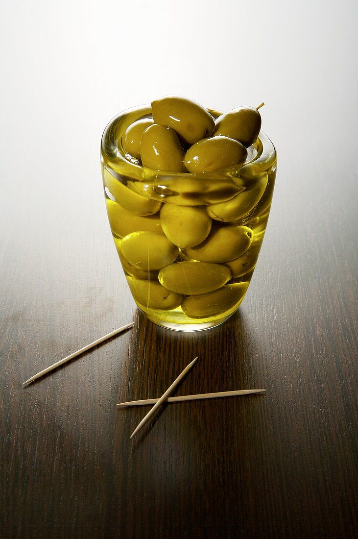 Green olives and olive oil in a glass