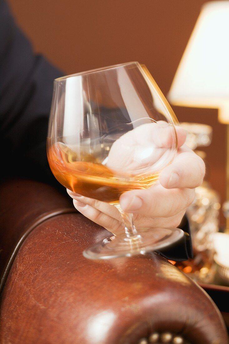 Man swirling cognac in a glass