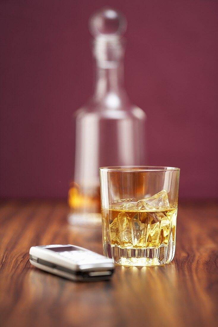 Whisky in glass and carafe, mobile phone