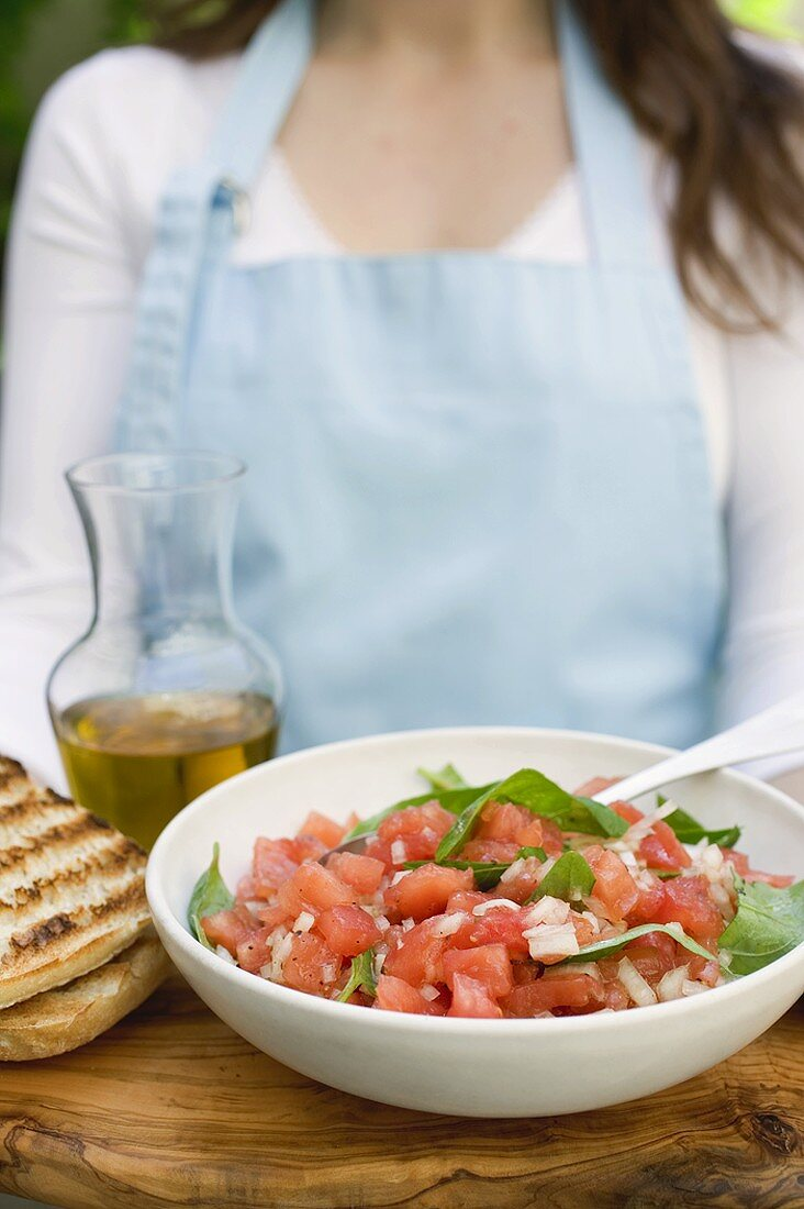 Woman serving tomato salsa with toasted bread & olive oil