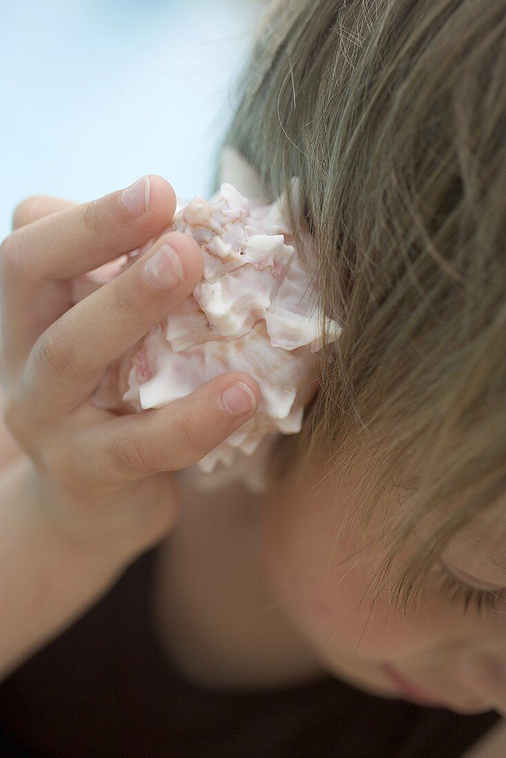Child holding a sea shell to its ear