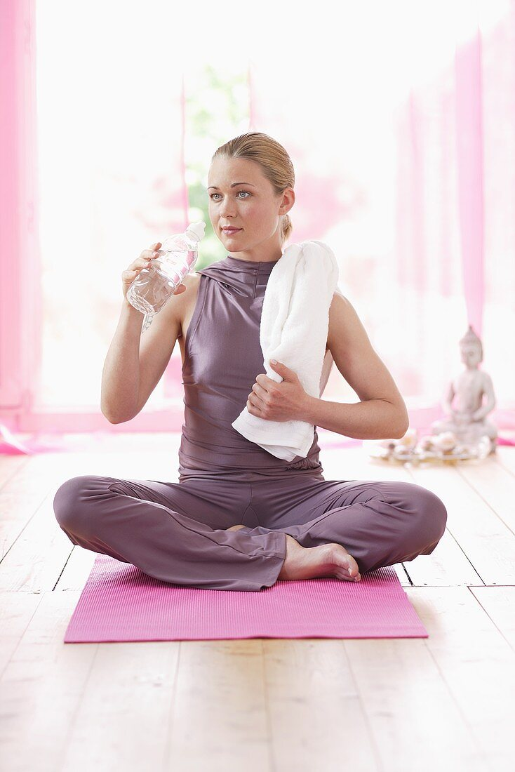 Woman in lotus position holding bottle of water
