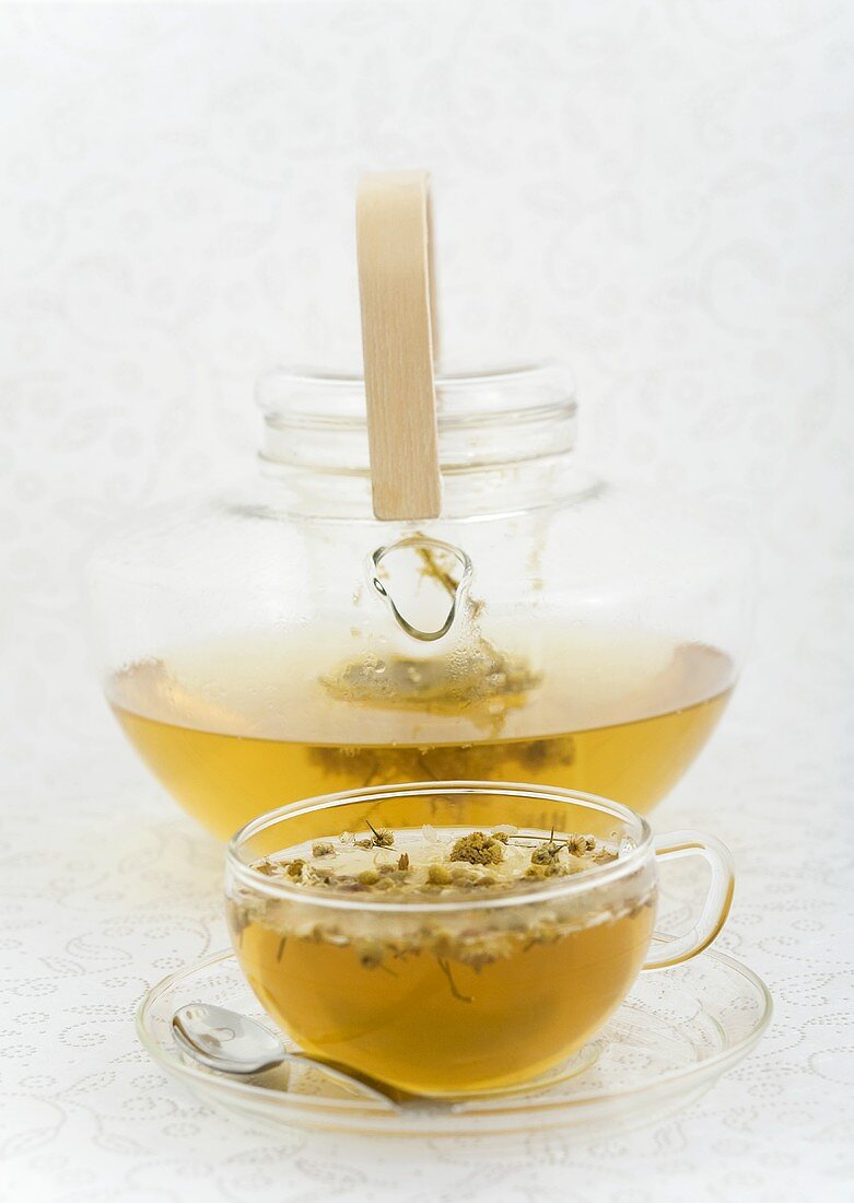Chamomile tea in glass cup and glass pot