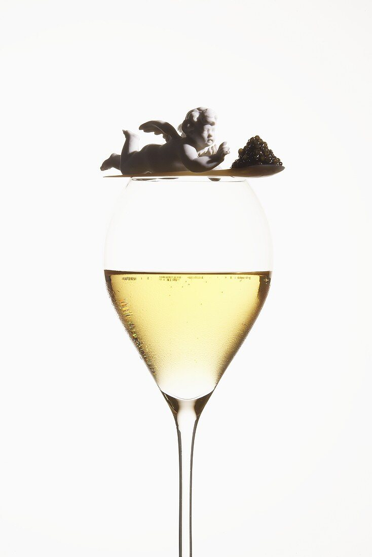 Spoonful of caviar with angel on glass of champagne