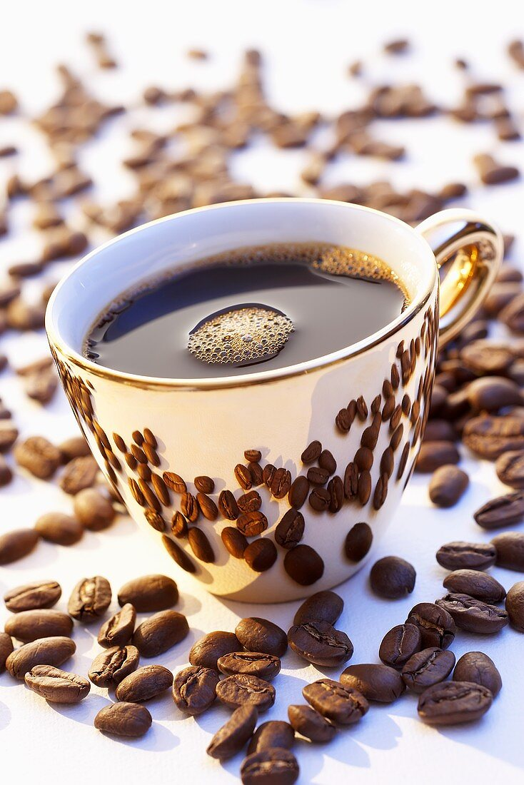A golden cup of coffee surrounded by coffee beans