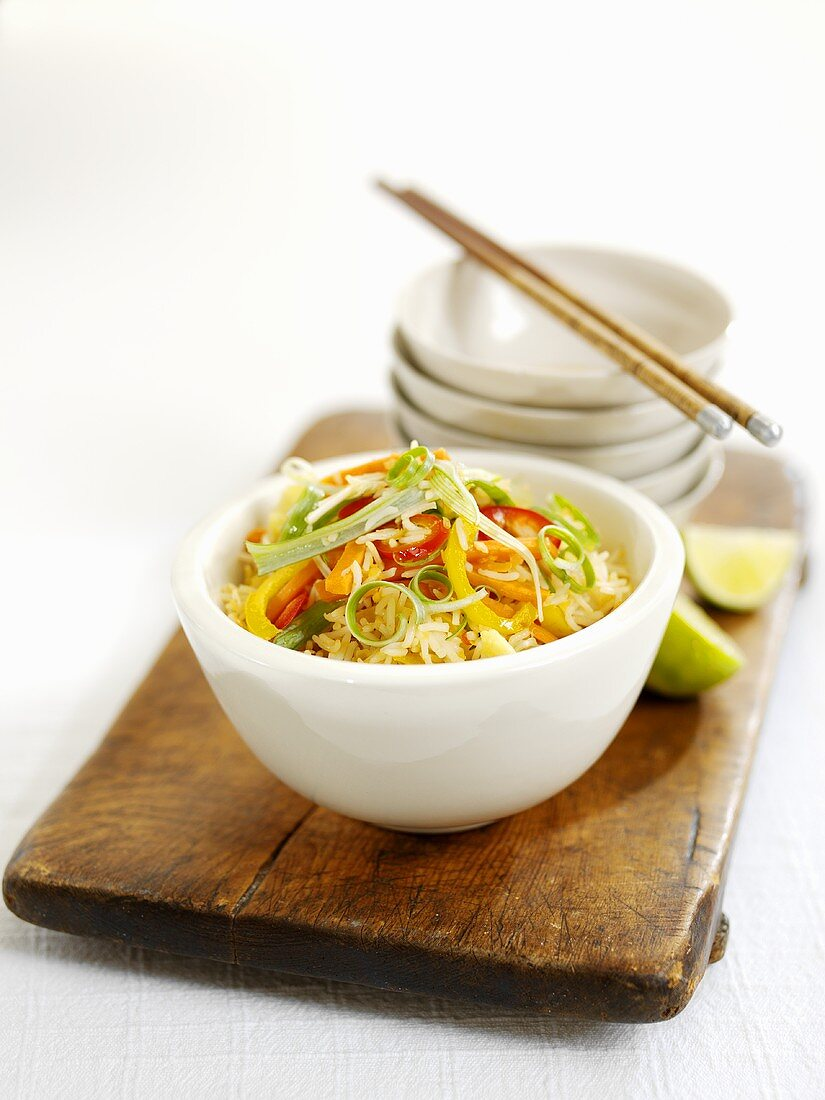 Rice dish with vegetables and pile of bowls
