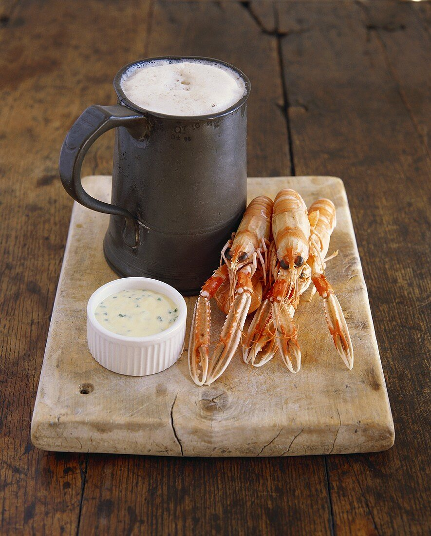 Several cooked freshwater crayfish with herb dip and beer