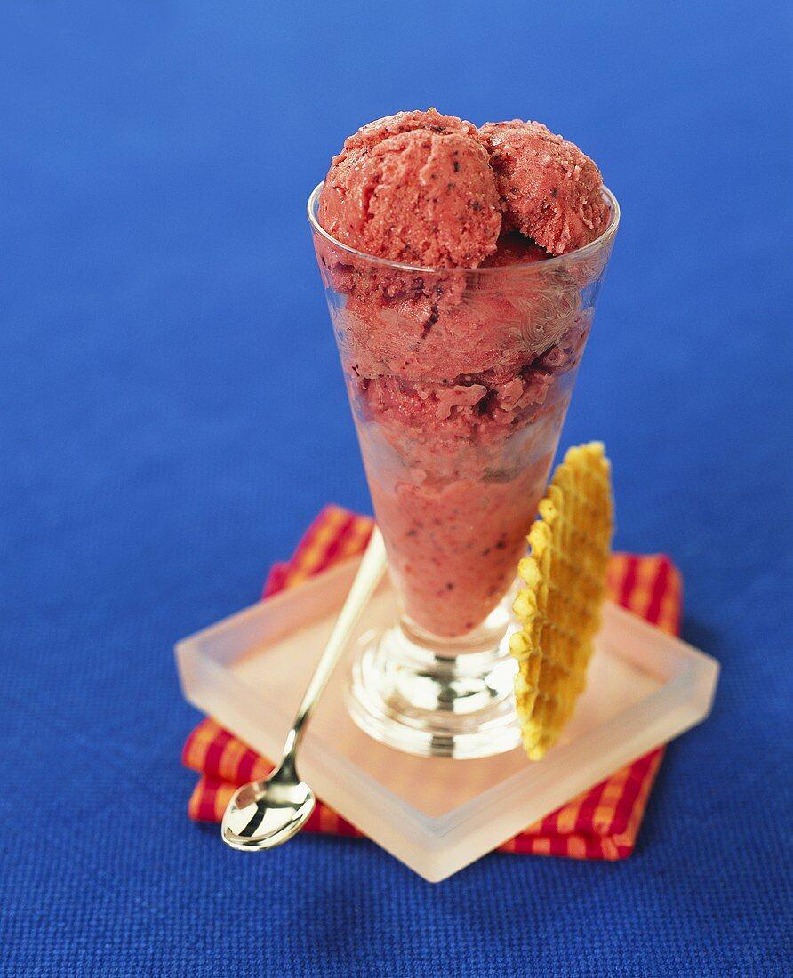 An ice cream sundae with blackberry ice cream and wafer