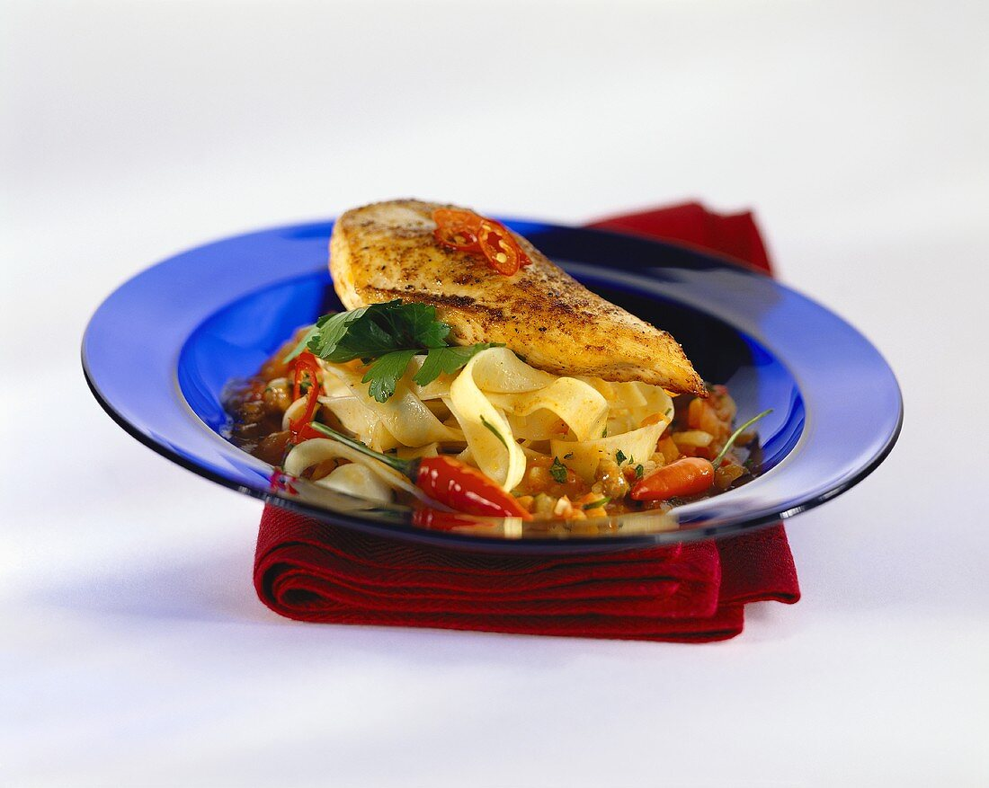 Chicken breast on pasta with chili sauce