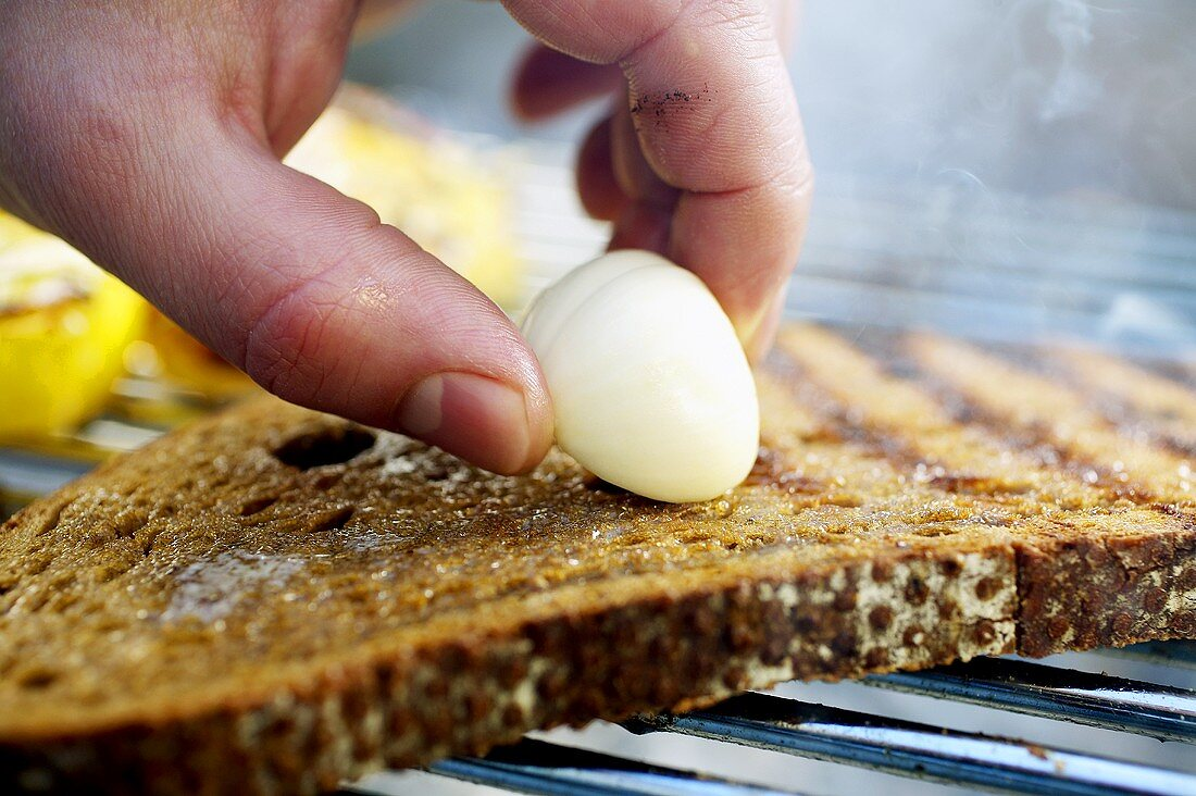 Barbecued bread being rubbed with garlic