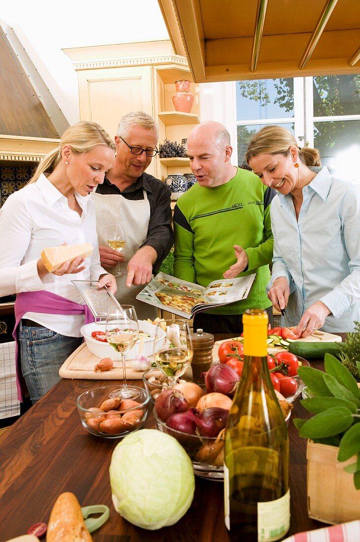Women preparing food, men consulting cookery book