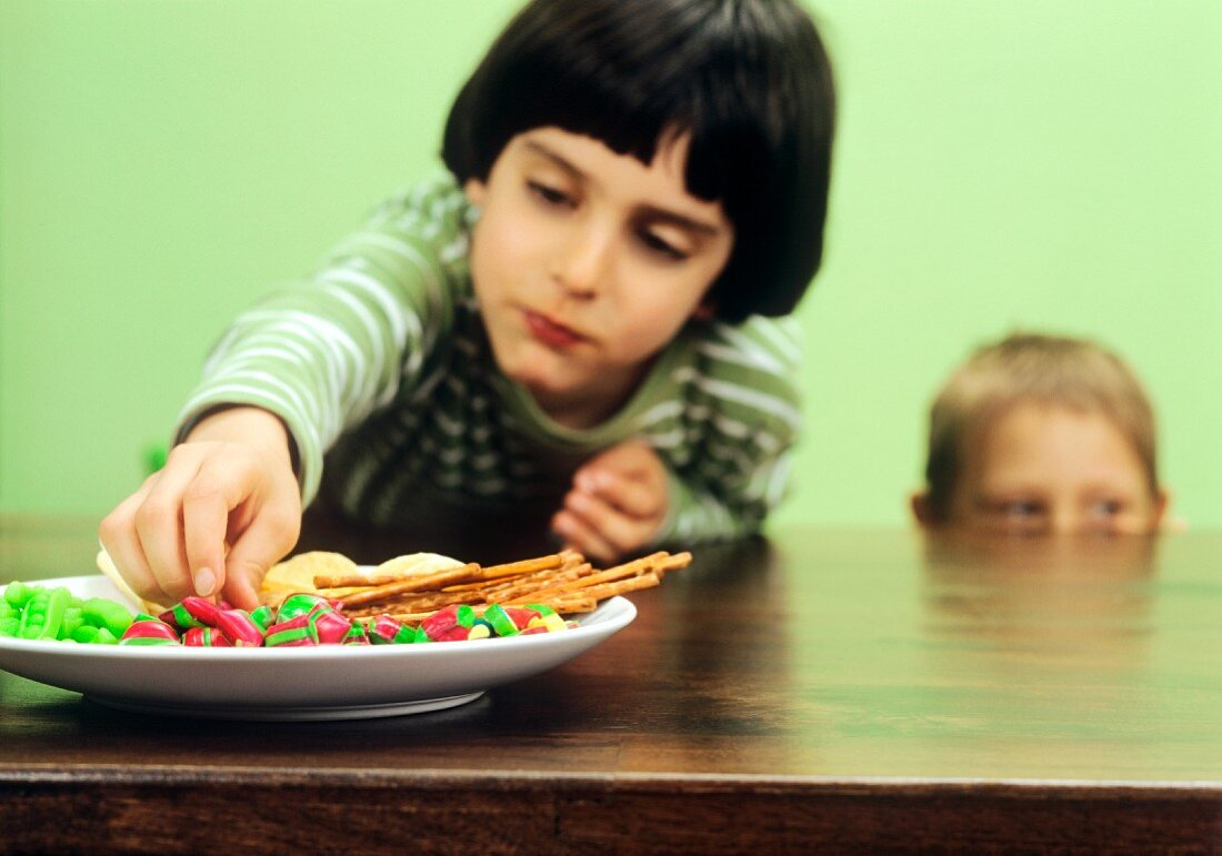 Boy reaching for sweets on a table