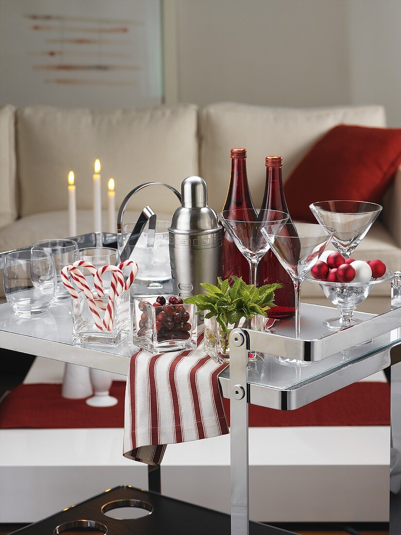 Bar utensils, candy canes and candles on serving trolley