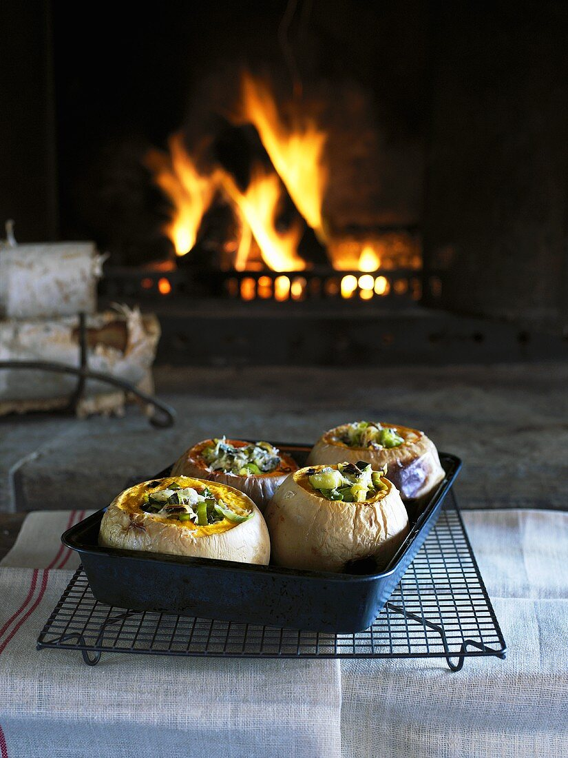 Pumpkins stuffed with vegetables in front of open fire
